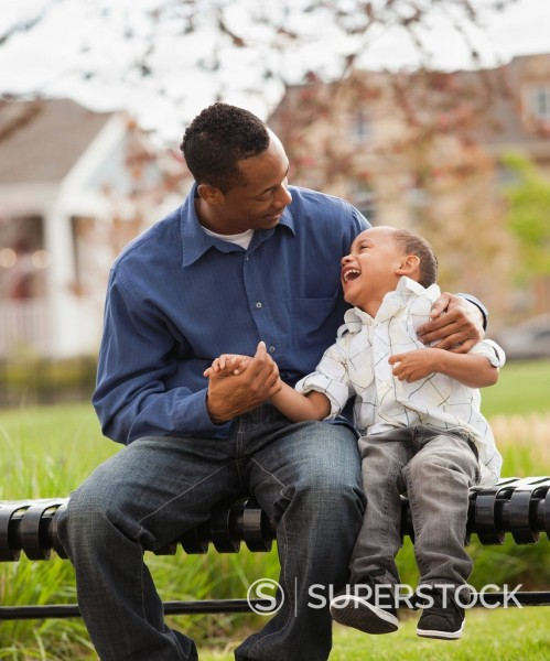 Father and son sitting together on park bench : Stock Photo