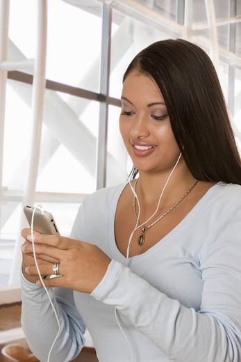 Stock Photo: 1589R-144773 Hispanic woman listening to mp3 player