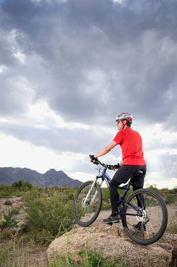 Caucasian man riding mountain bike in remote area : Stock Photo