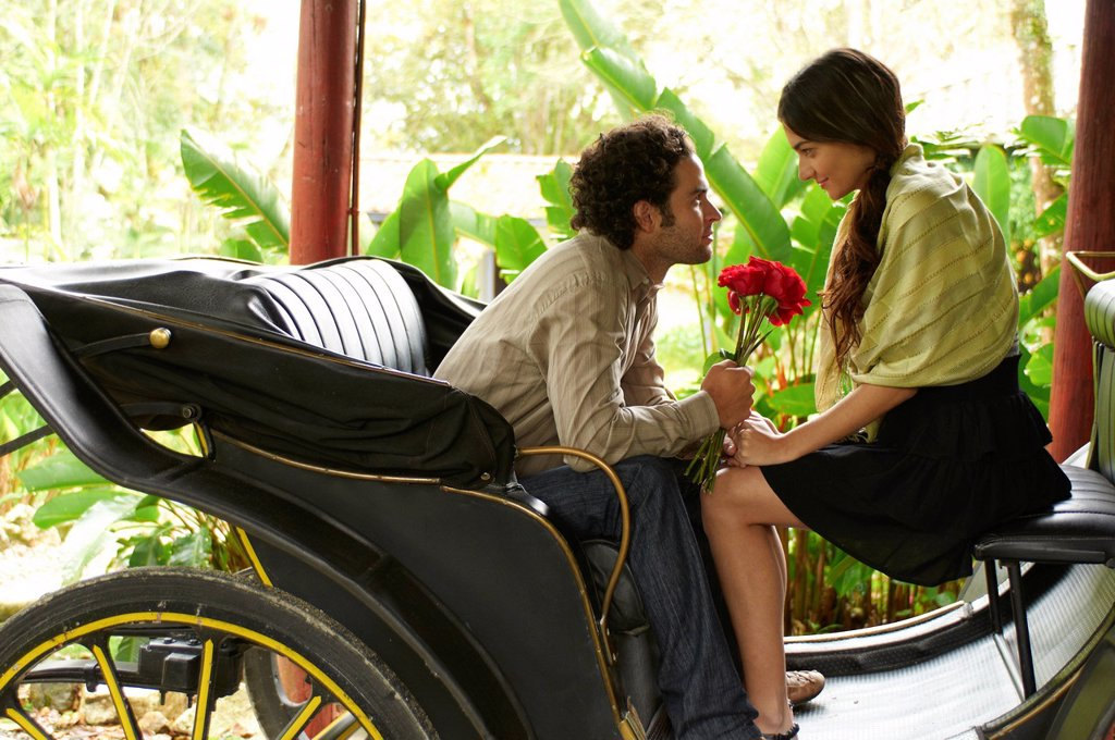 Hispanic man sitting in carriage giving girlfriend roses : Stock Photo
