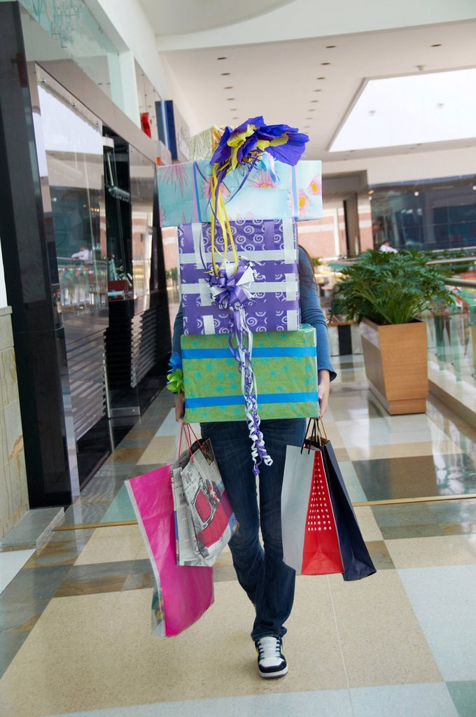 Stock Photo: 1589R-145295 Hispanic teenager carrying gifts in shopping mall