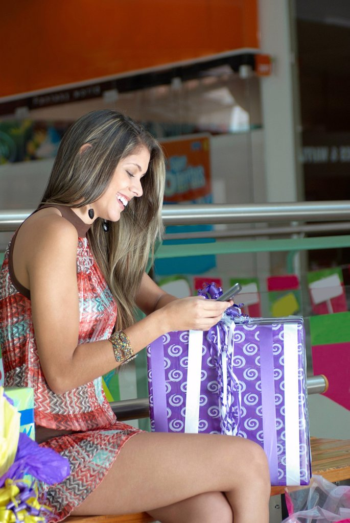 Hispanic woman holding gift and using cell phone : Stock Photo
