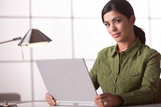 Hispanic woman sitting with laptop : Stock Photo