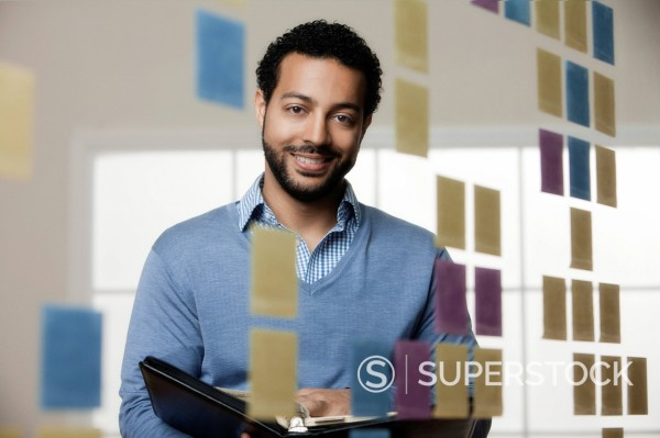 Stock Photo: 1589R-145422 Mixed race businessman looking at sticky notes in office