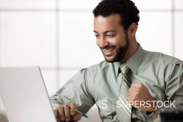 Mixed race businessman looking at laptop cheering : Stock Photo