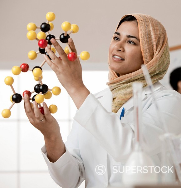 Stock Photo: 1589R-145437 Mixed race scientist in hijab looking at molecule model