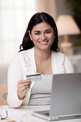 Mixed race woman shopping online with credit card : Stock Photo