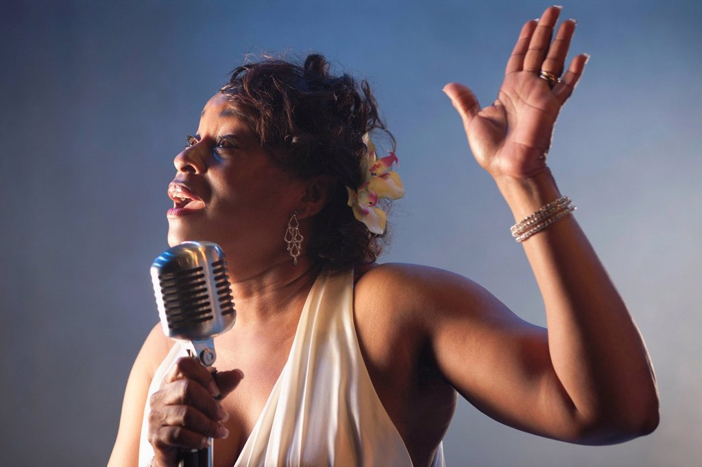 Black woman singing into microphone : Stock Photo