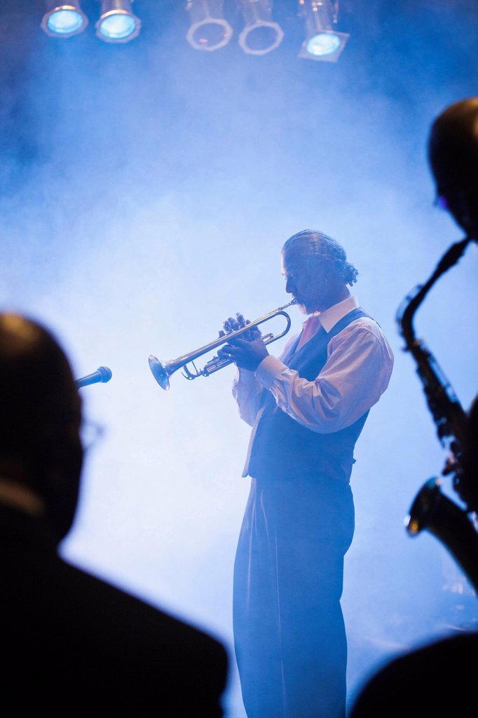 Musician playing trumpet on stage : Stock Photo