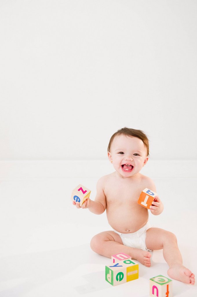 Mixed race baby playing with alphabet blocks : Stock Photo