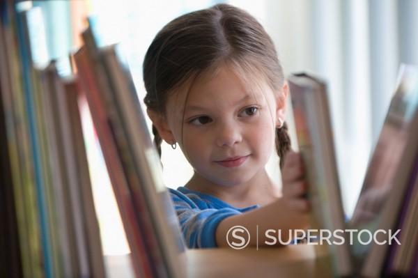 Caucasian girl taking book from shelf : Stock Photo