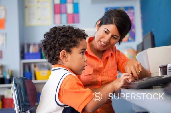 Stock Photo: 1589R-146121 Teacher helping student use computer in classroom