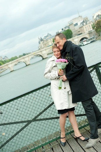 Caucasian couple hugging on bridge : Stock Photo