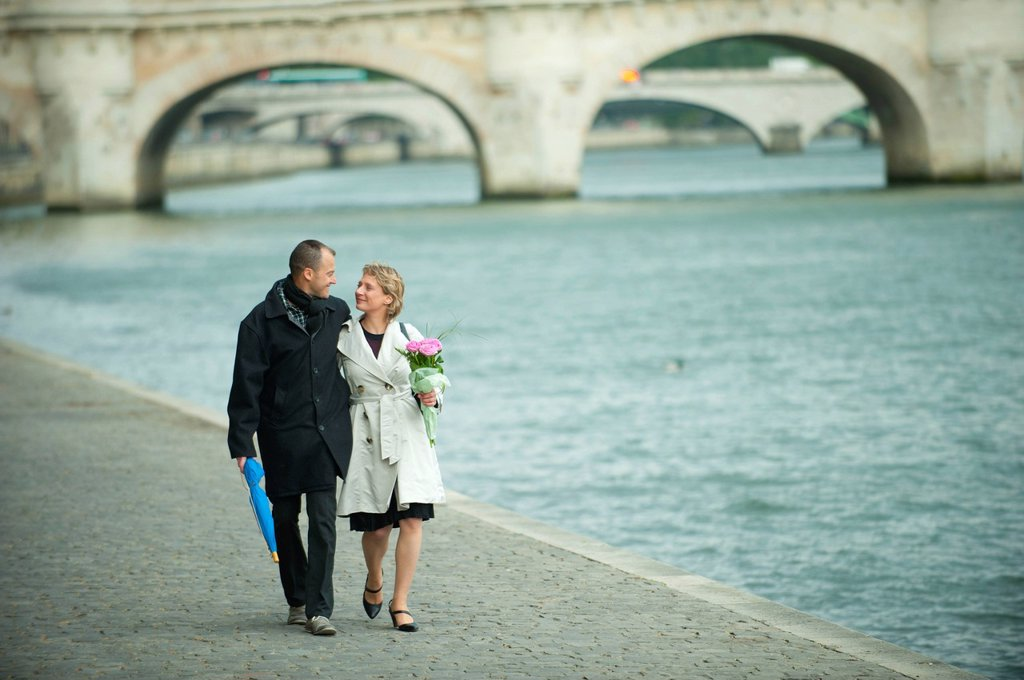Caucasian couple walking near city river : Stock Photo