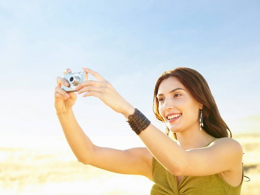 Beautiful woman in nature taking a photograph with a point and shoot digital camera : Stock Photo