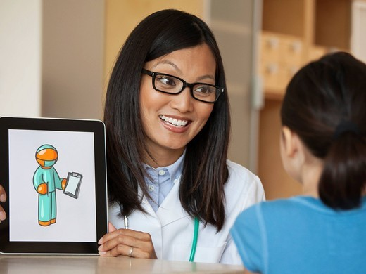 Doctor using digital tablet to explain healthcare to girl : Stock Photo