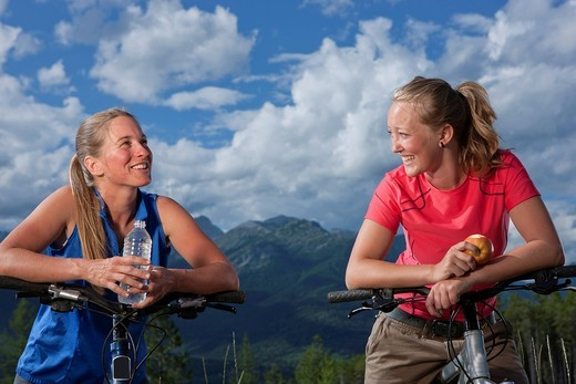 Friends standing with mountain bikes drinking water : Stock Photo