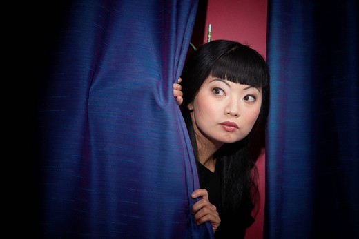 Anxious Asian woman peering out from behind stage curtains : Stock Photo
