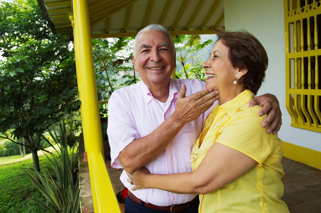 Senior Hispanic couple hugging on porch : Stock Photo