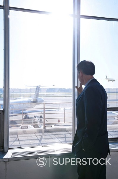 Stock Photo: 1589R-146748 Caucasian businessman watching airplanes in airport