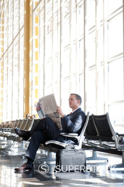 Caucasian businessman reading newspaper in airport : Stock Photo