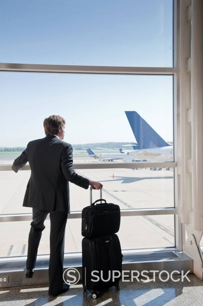 Stock Photo: 1589R-146761 Caucasian businessman watching airplanes in airport