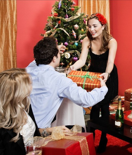Woman handing gift to man at Christmas party : Stock Photo