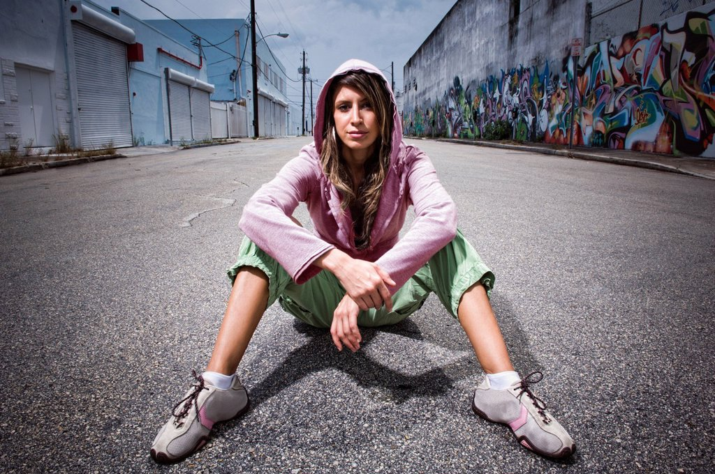 Stock Photo: 1589R-146860 Hispanic woman sitting in alley with graffiti