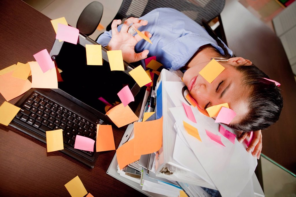 Hispanic businesswoman covered in sticky notes sleeping at desk : Stock Photo