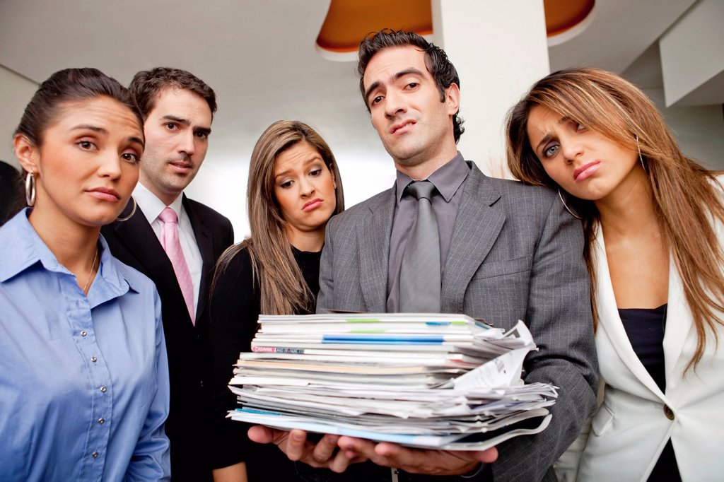 Stock Photo: 1589R-146994 Frustrated Hispanic business people with pile of paperwork