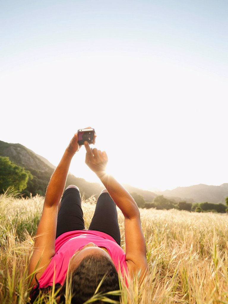Black woman laying in field using cell phone : Stock Photo