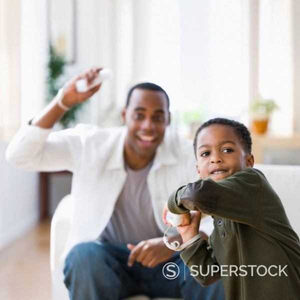 Stock Photo: 1589R-147225 African American father and son playing video game