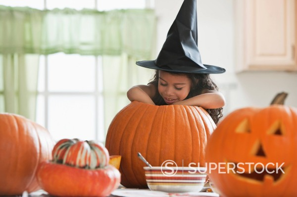 Stock Photo: 1589R-147361 Hispanic girl in witch´s hat carving a pumpkin