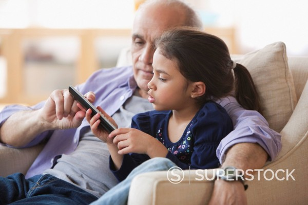 Grandfather and granddaughter watching television together : Stock Photo