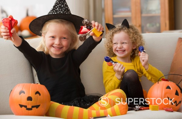 Stock Photo: 1589R-147654 Caucasian girls in Halloween costumes eating candy