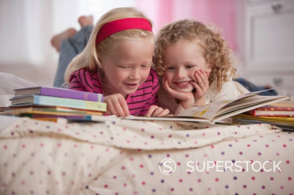 Stock Photo: 1589R-147671 Caucasian girls laying on bed reading books