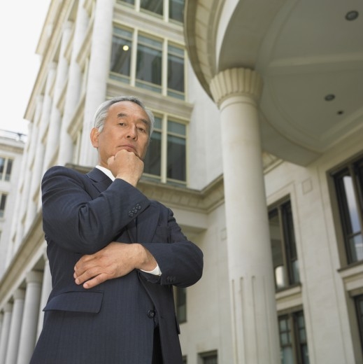 Stock Photo: 1589R-14768 Low angle view of senior Asian businessman posing