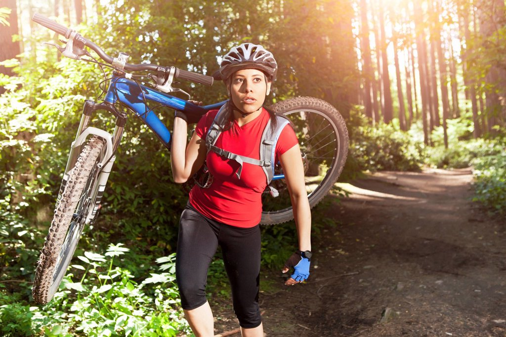 Stock Photo: 1589R-147868 Hispanic woman carrying mountain bike in forest