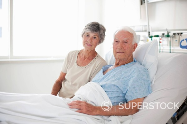 Wife sitting with husband in hospital bed : Stock Photo