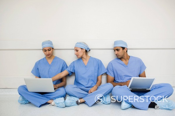 Stock Photo: 1589R-148257 Doctors sitting on floor using laptops
