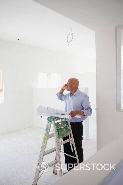Hispanic architect holding blueprints and talking on cell phone : Stock Photo