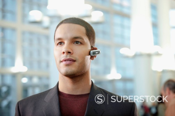 Stock Photo: 1589R-148858 Hispanic businessman wearing hands_free cellular device