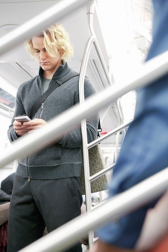 Caucasian businessman text messaging on cell phone on subway train : Stock Photo
