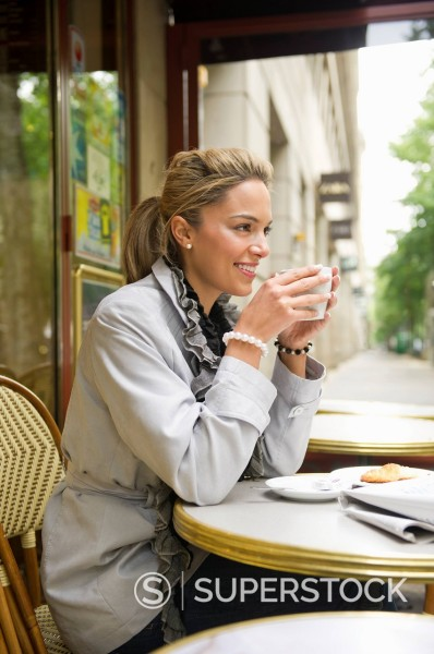 Hispanic woman drinking coffee in outdoor cafe : Stock Photo