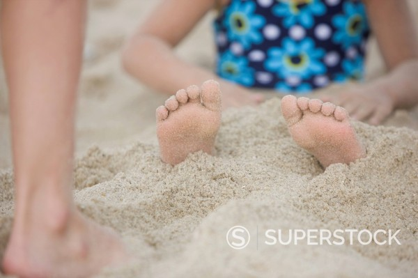 Stock Photo: 1589R-148975 Caucasian girl buried in the sand on beach