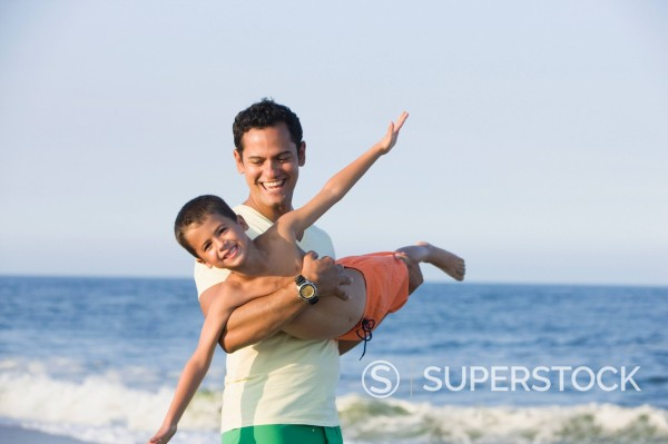 Stock Photo: 1589R-149002 Father swinging son on beach