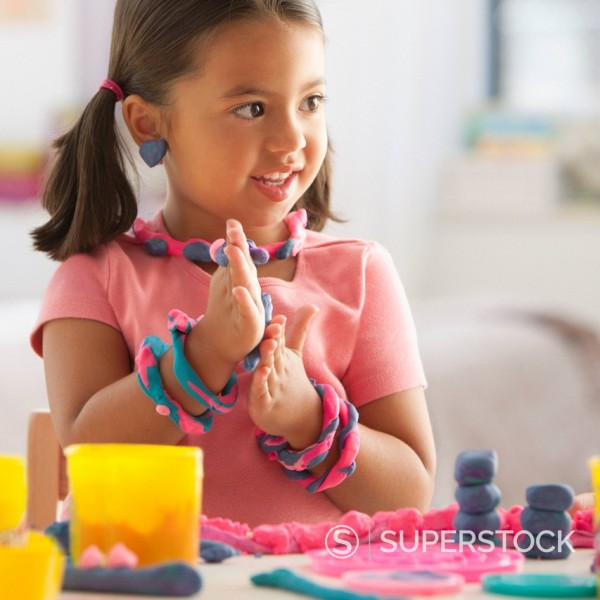 Caucasian girl playing with clay : Stock Photo
