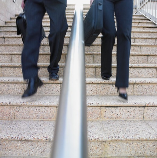 Businesspeople descending a staircase : Stock Photo