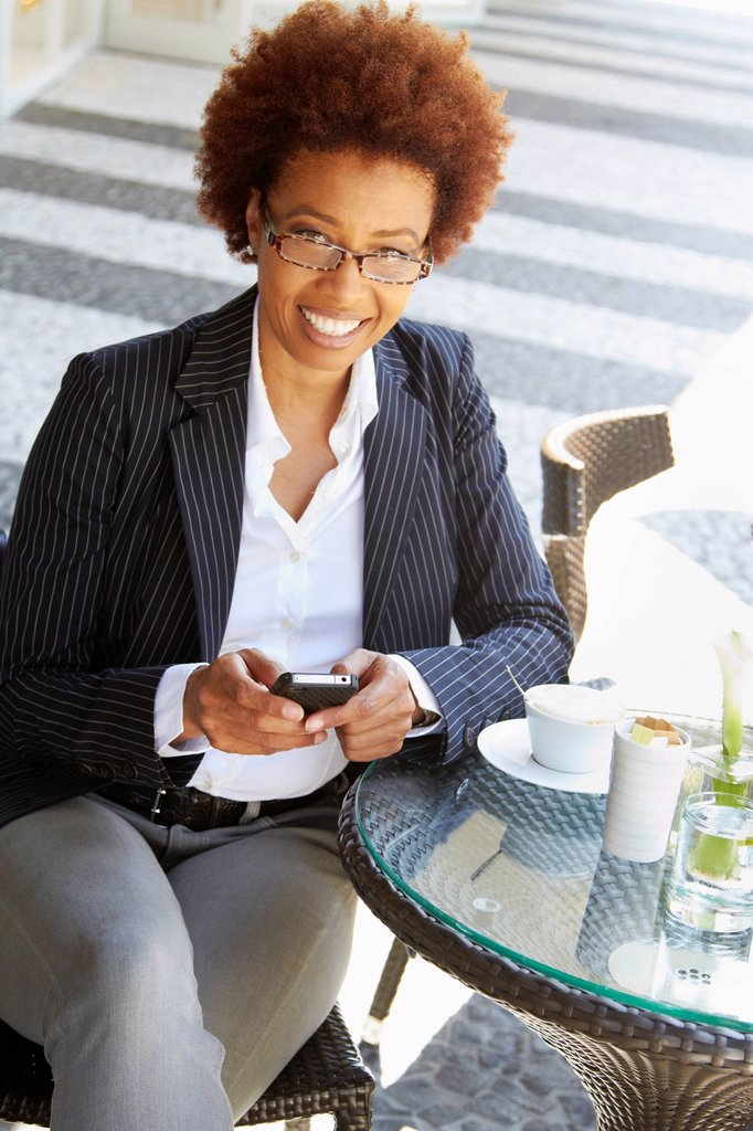 Stock Photo: 1589R-149279 African American woman text messaging on cell phone at sidewalk cafe