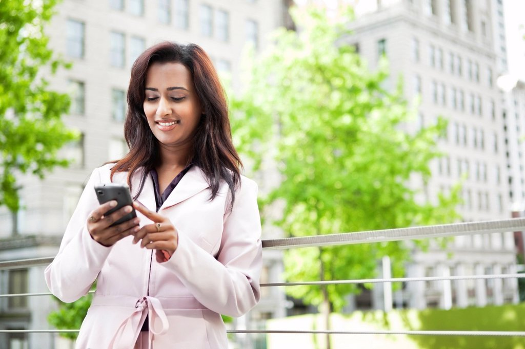 Stock Photo: 1589R-149322 Indian businesswoman text messaging on cell phone